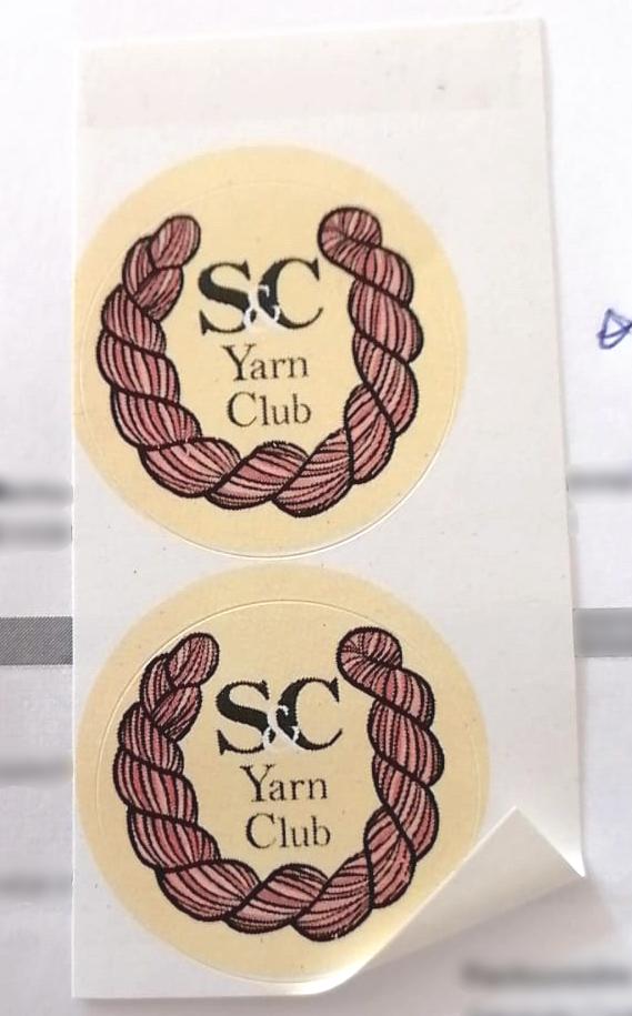 Een foto van twee stickers op een vel van het S&C Yarn Club logo