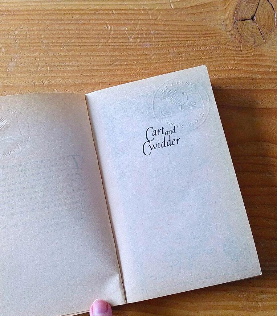 Een foto van de titelpagina van de roman Cart and Cwidder met een persoonlijk Ex Libris logo in reliëf erin gedrukt