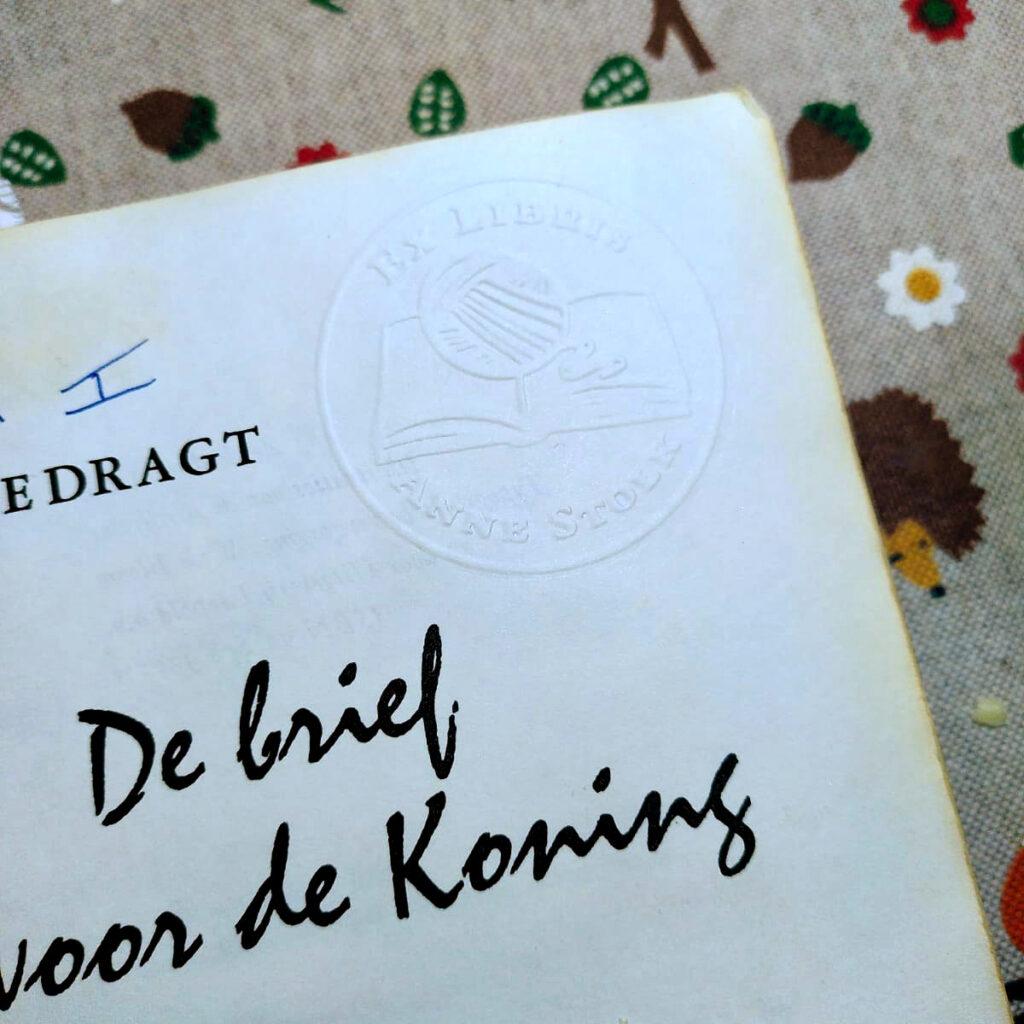 Een foto van de titelpagina van de roman De Brief voor de Koning met een persoonlijk Ex Libris logo in reliëf erin gedrukt